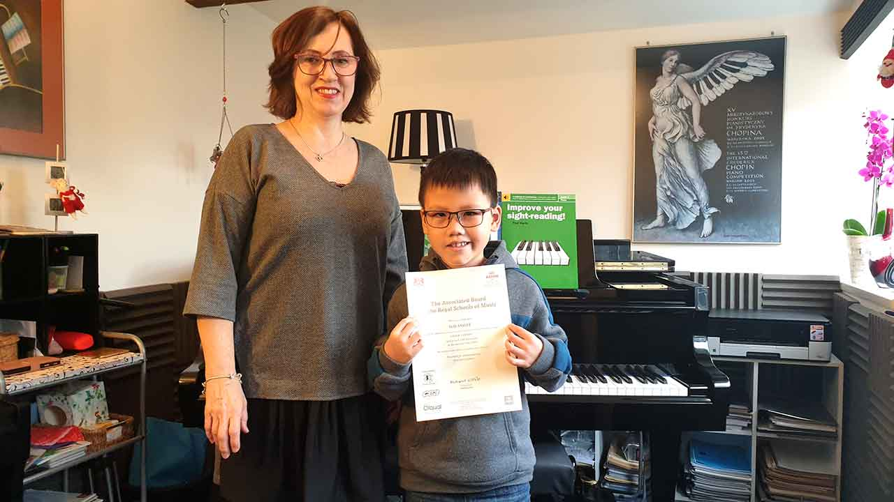 Anna Peszko presenting Hai Anh Le with his ABRSM Grade 1 Distinction certificate