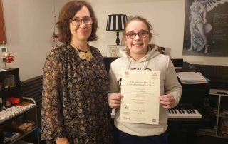 Anna Peszko presenting Isobel with her ABRSM Grade 1 Merit certificate