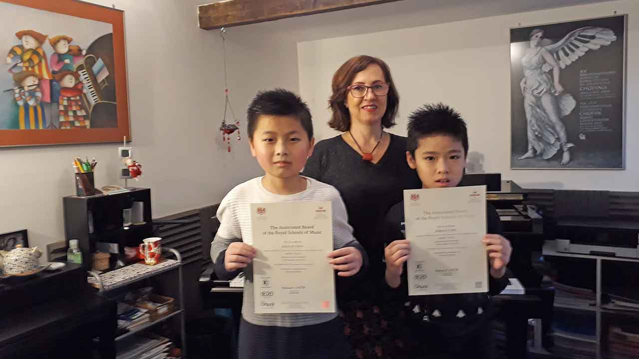 Anna Peszko presenting Keenan and Jordan with their ABRSM Grade 1 Distinction certificates