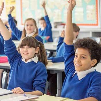 School children rasing hand in class